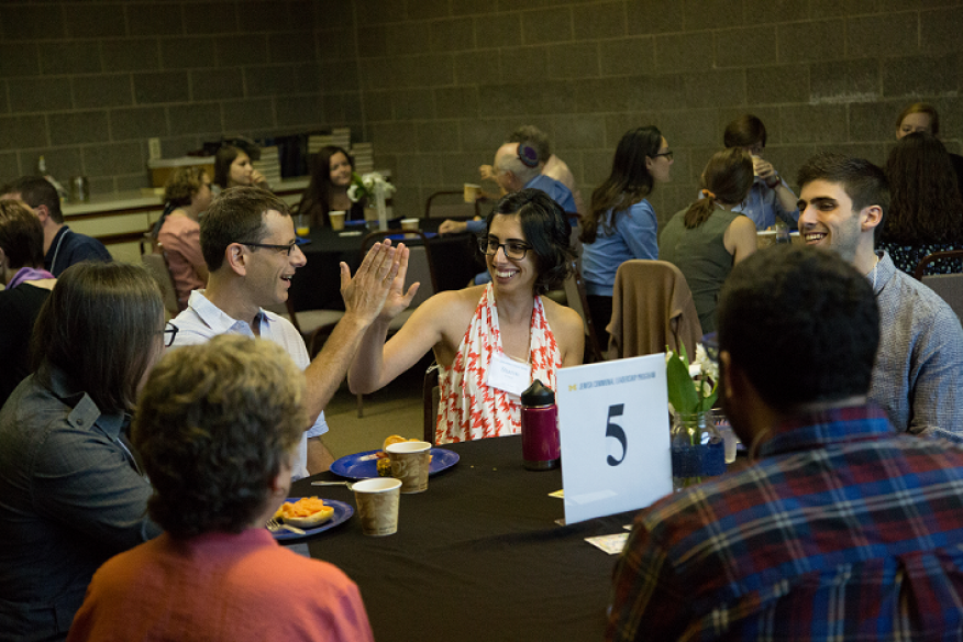 Two people high fiving around the table at the 2016 Community Welcome Breakfast.
