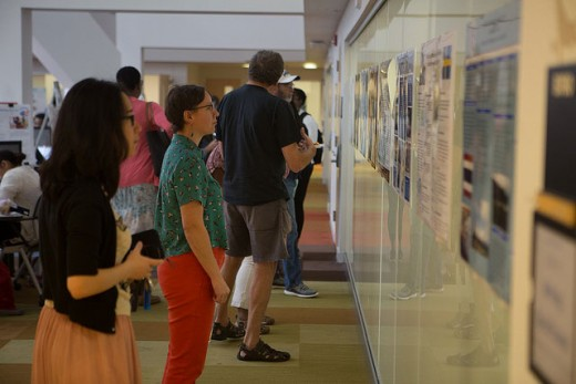 Students observe posters on the wall of the SSW lower level.